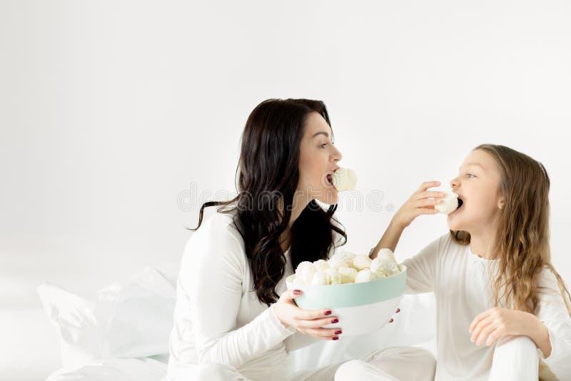 Filha e mãe que sentam-se na cama e que comem marshmallows em casa foto de stock royalty free
