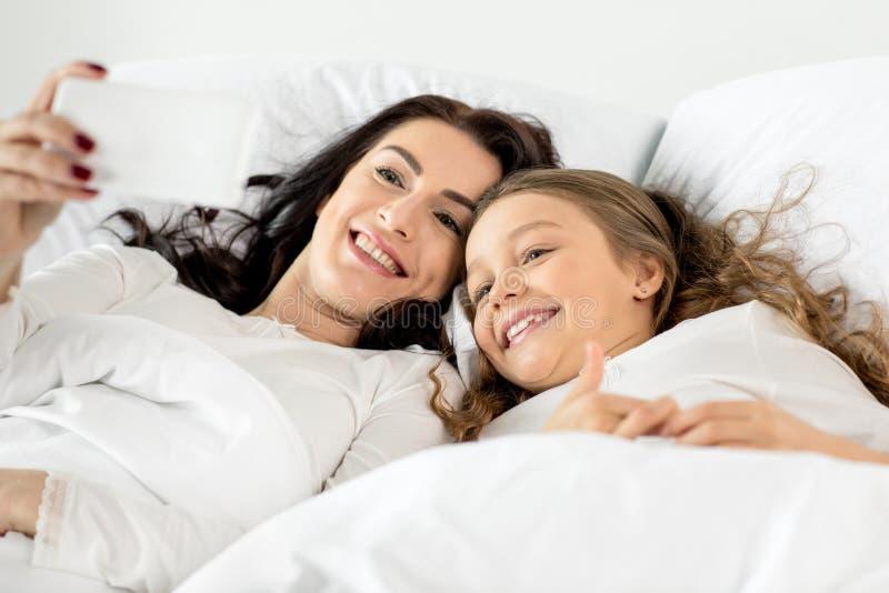 Filha e mãe que tomam o selfie no smartphone ao encontrar-se na cama imagens de stock