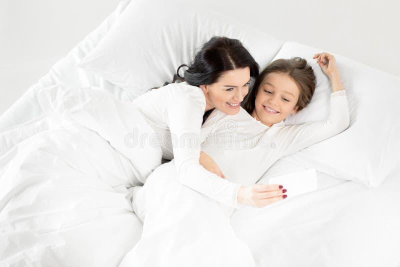 Filha e mãe que tomam o selfie no smartphone ao encontrar-se na cama imagem de stock