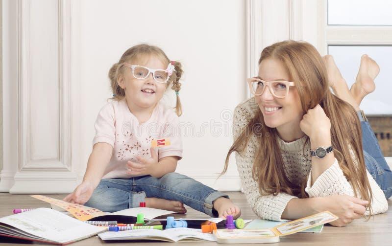 A filha e a mãe sentam-se no assoalho e na tração imagem de stock