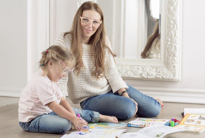 A filha e a mãe sentam-se no assoalho e na tração foto de stock royalty free