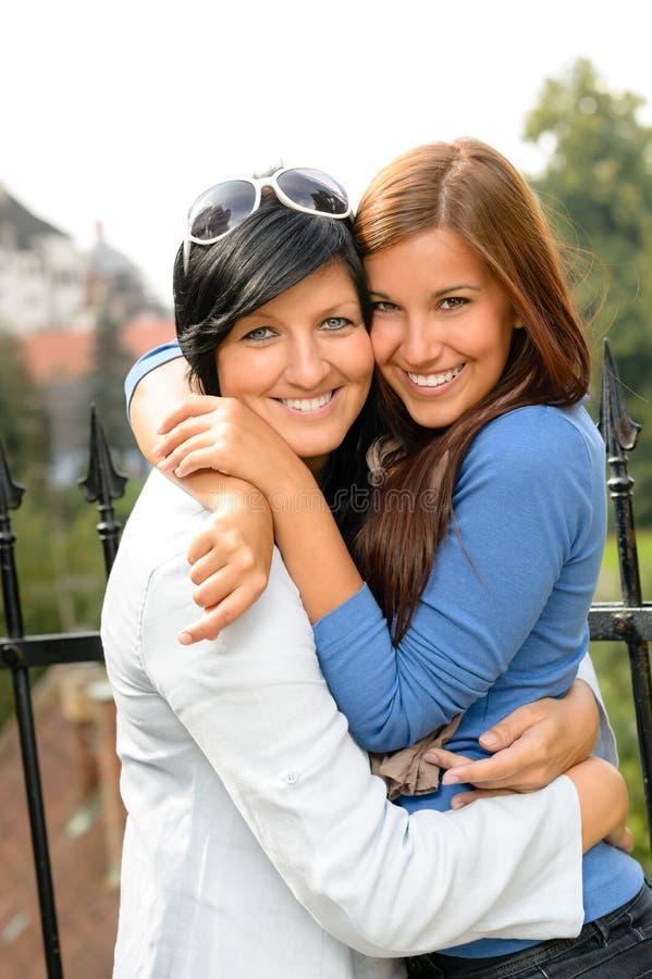 Filha e matriz que abraçam ao ar livre adolescente feliz fotos de stock