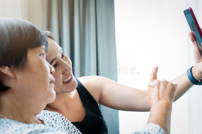 Filha e sua mãe que fazem um selfie usando o telefone esperto e o sorriso imagens de stock