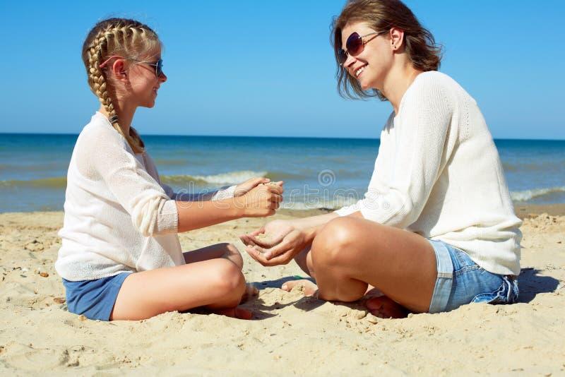 Filha e sua mam? que jogam com a areia na praia fotografia de stock royalty free