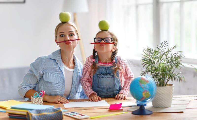 Filha engraçada da mãe e da criança que faz a escrita e o readi dos trabalhos de casa imagens de stock royalty free