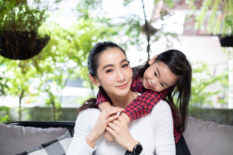 A filha está abraçando seus mãe e riso felizes fotos de stock royalty free
