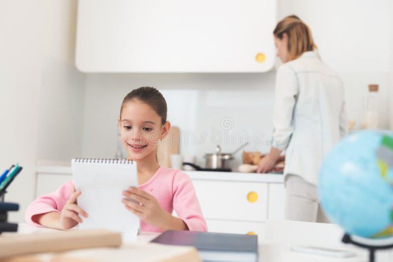 A filha faz as lições quando a mamã preparar o jantar fotos de stock royalty free