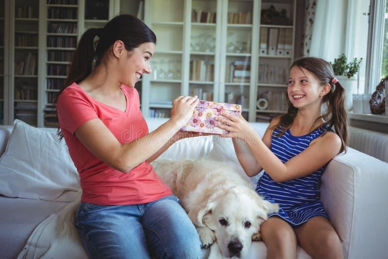 Filha feliz que dá um presente da surpresa à mãe foto de stock