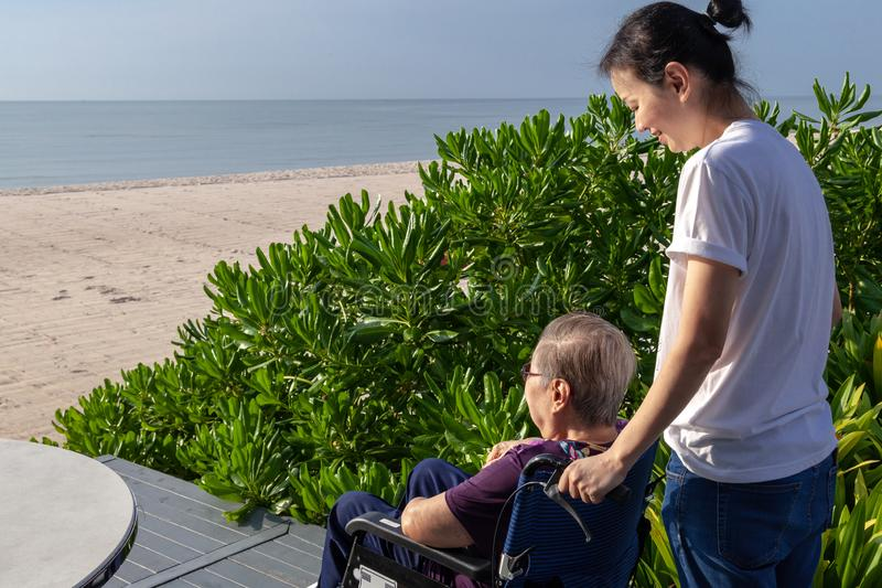 A filha incrementa a cadeira de rodas para a frente sua mãe na frente da praia fotografia de stock
