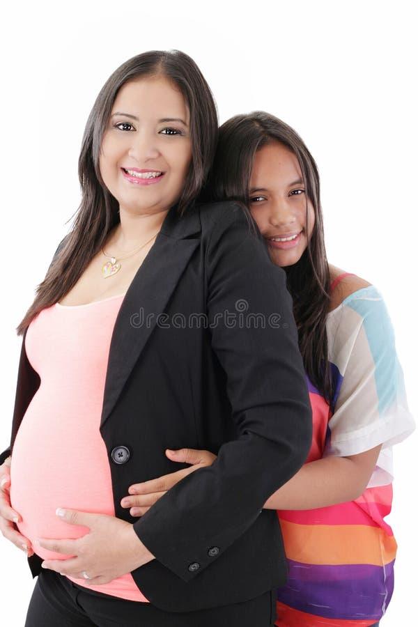 Filha latino-americano que abraça sua mulher de negócios Pregnant Mother fotografia de stock royalty free