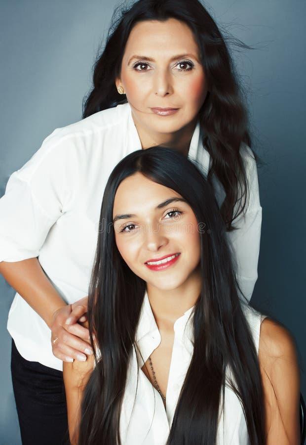 Filha linda e adolescente com mãe madura se abraçando, morena de estilo de moda, pessoas conceituadas para estilo de vida se apro fotografia de stock
