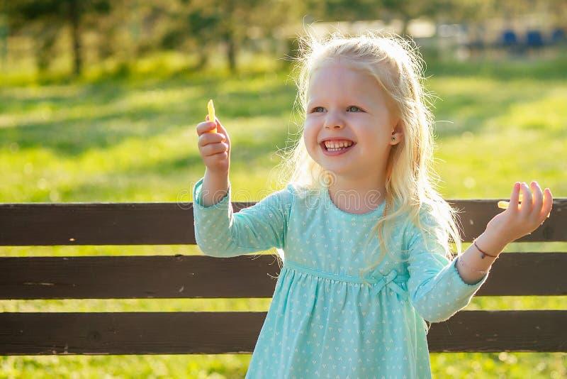 Filha linda loira comendo batatas fritas em um banco no parque alimentos pouco saudáveis na infância foto de stock
