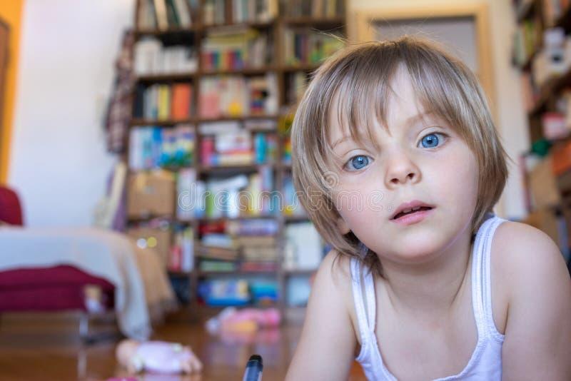 Filha loura da menina com os olhos azuis que olham a câmera na sala de visitas Vida familiar relaxado feliz com crianças em casa fotografia de stock