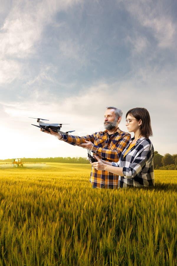 A filha mostra a nova tecnologia do pai da agronomia inovação na indústria em torno do campo da colheita foto de stock