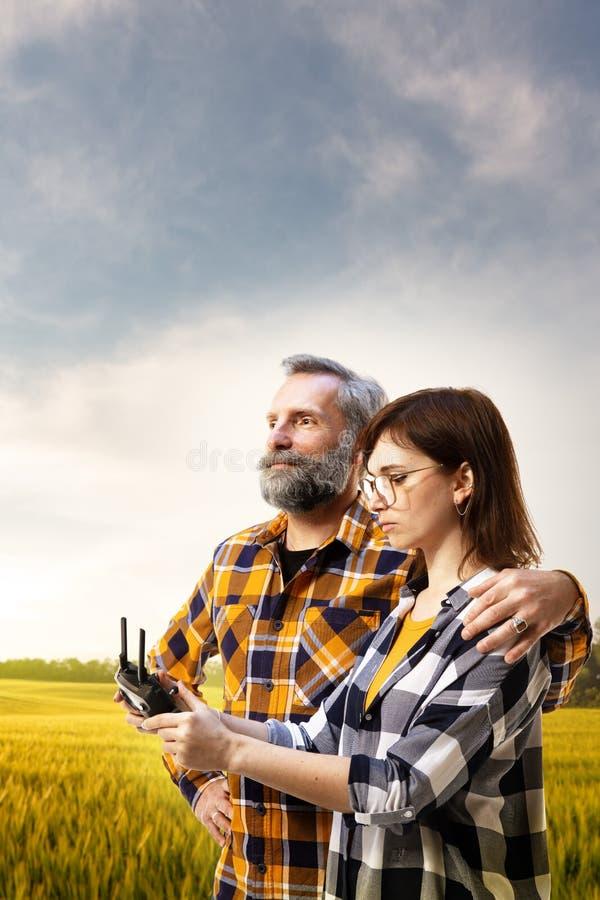 A filha mostra a nova tecnologia do pai da agronomia inovação na indústria em torno do campo da colheita fotografia de stock royalty free