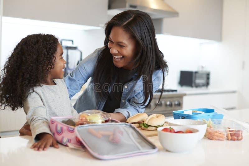 Filha na cozinha em casa que ajuda a mãe a fazer o almoço embalado saudável foto de stock