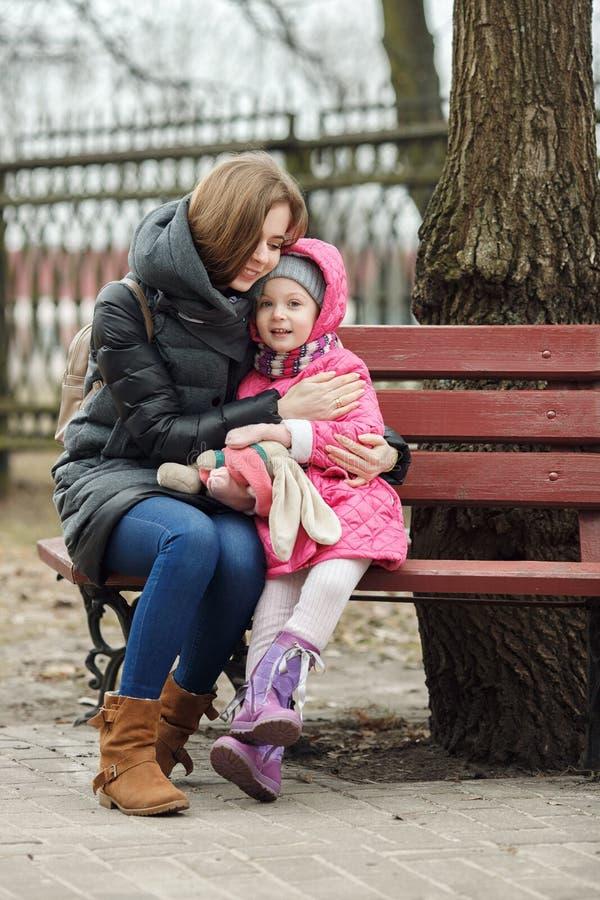 Filha nova feliz da mãe e da criança que abraça o assento no banco no parque da mola fotografia de stock