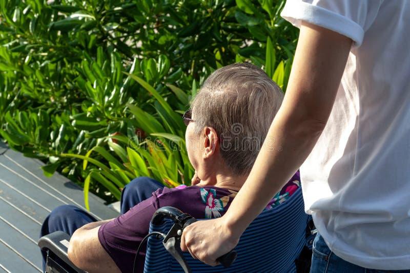 A filha ou o filho incrementam a cadeira de rodas para a frente sua mãe na frente da praia foto de stock