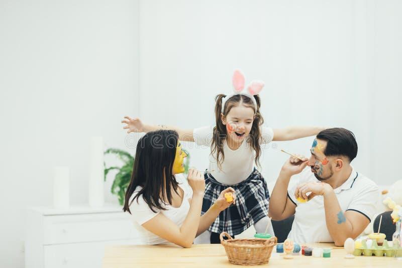 A filha pequena bonito com tranças e orelhas do coelho está abraçando seus pais Ovos da páscoa de pintura da mãe e do pai fotos de stock