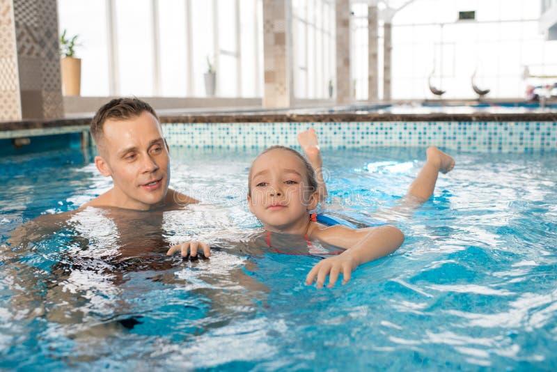 Filha pequena de ensino a nadar foto de stock royalty free