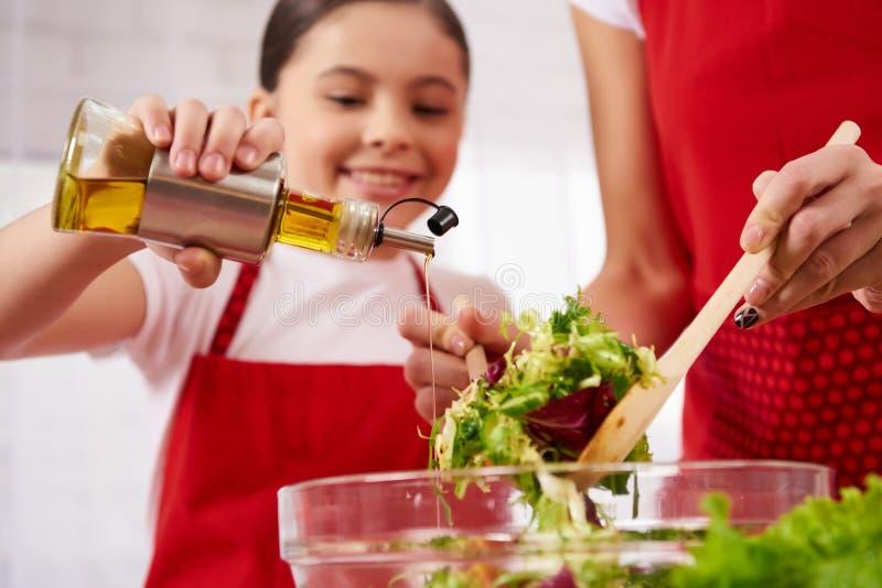 A filha pequena derrama o azeite na salada fotos de stock royalty free
