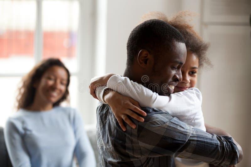 Filha pequena do abraço preto loving do pai em casa fotos de stock