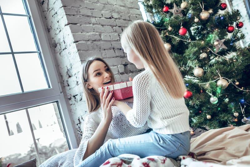 Filha pequena feliz que dá o presente do Natal da mãe em casa imagens de stock royalty free