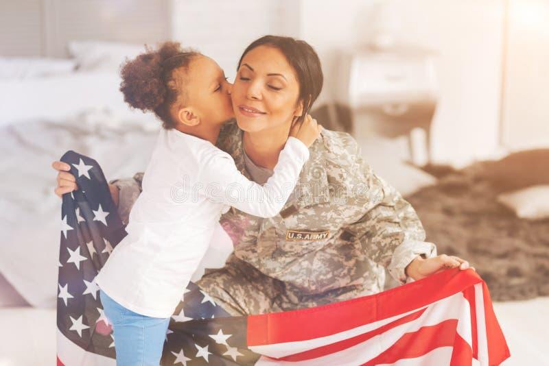 Filha pequena que beija sua mãe que guarda a bandeira dos E.U. fotos de stock