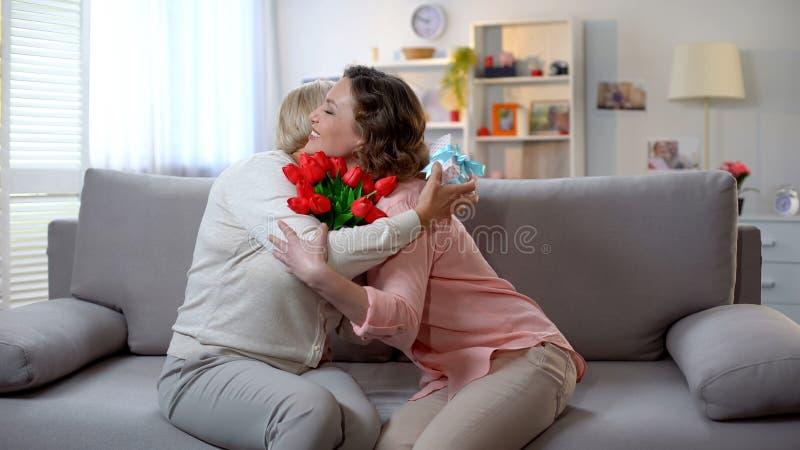 Filha que abraça a mãe superior, mulher que guarda tulipas e felicitações da caixa de presente imagens de stock royalty free