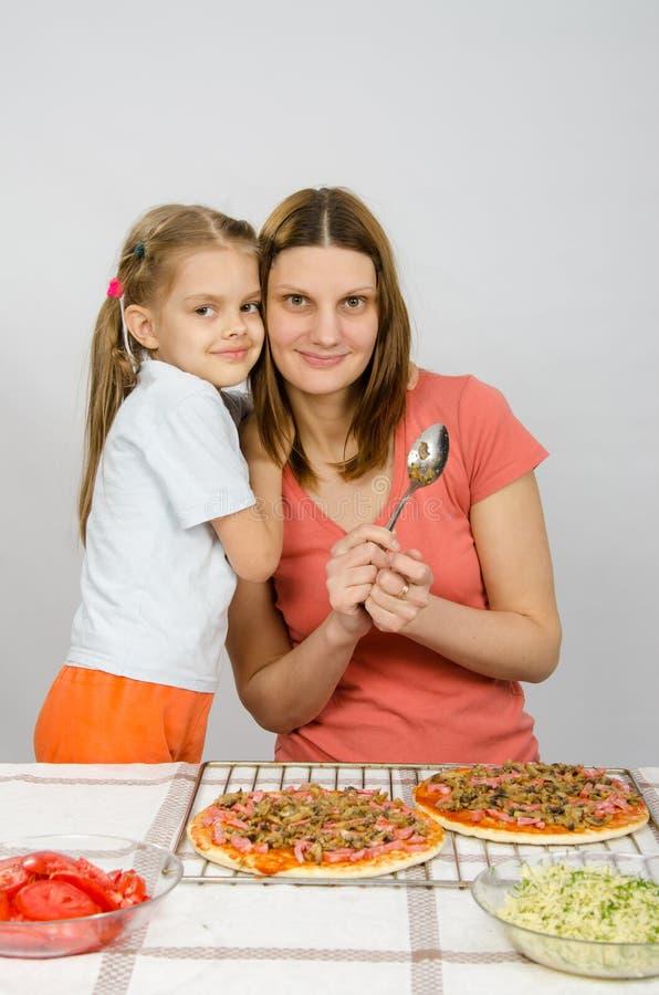 Filha que abraça sua mãe seis anos, que está preparando a pizza imagens de stock royalty free