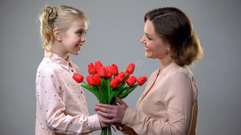 Filha que dá flores para serir de mãe, felicitações do dia da mulher, presente da surpresa foto de stock royalty free