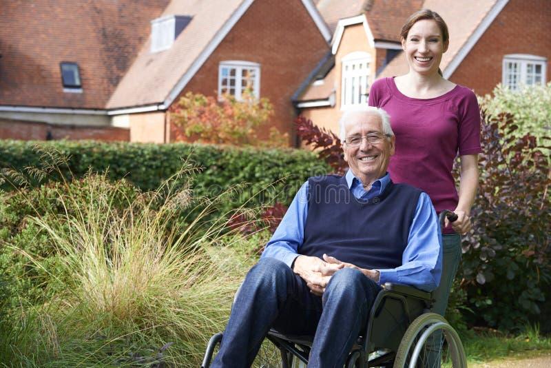 Filha que empurra o pai superior In Wheelchair fotografia de stock royalty free
