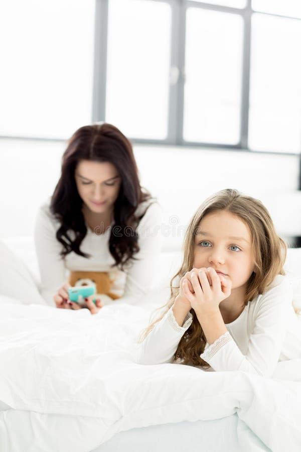 Filha que encontra-se na cama e na mãe com smartphone atrás em casa imagem de stock royalty free