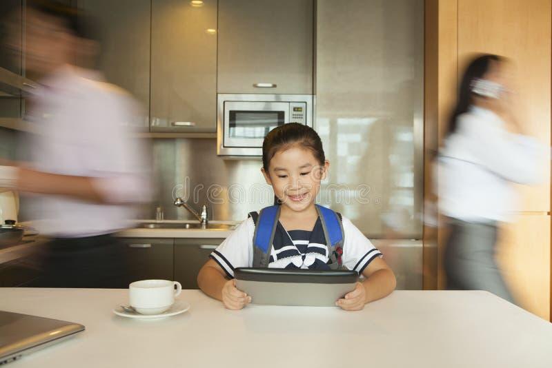 Filha que joga na tabuleta digital quando pais que correm ao redor fotografia de stock royalty free