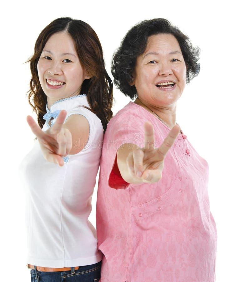 A filha superior da mãe e do adulto que mostra a paz entrega o sinal foto de stock royalty free