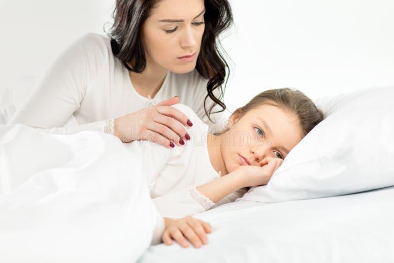 Filha virada e mãe que encontram-se na cama em casa foto de stock