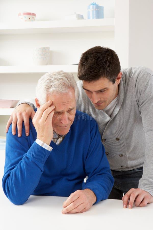 Filho acima crescido que consola o pai sênior foto de stock