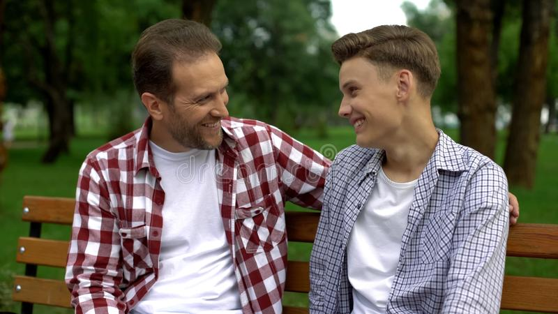 Filho adolescente que fala com o pai no banco, dizendo segredos e sorrindo, confiança fotografia de stock