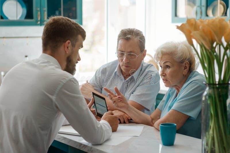 Filho adulto que mostra pais idosos foto de stock