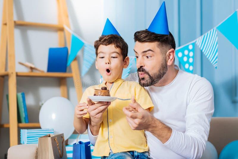 Filho alegre e pai que fundem para fora a vela no bolo de aniversário foto de stock