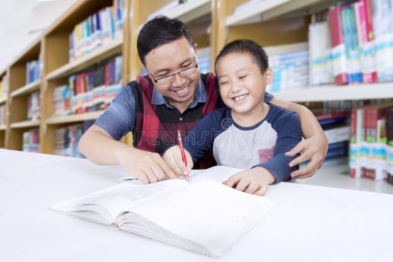 Filho asiático da ajuda do pai com seus trabalhos de casa na biblioteca fotografia de stock