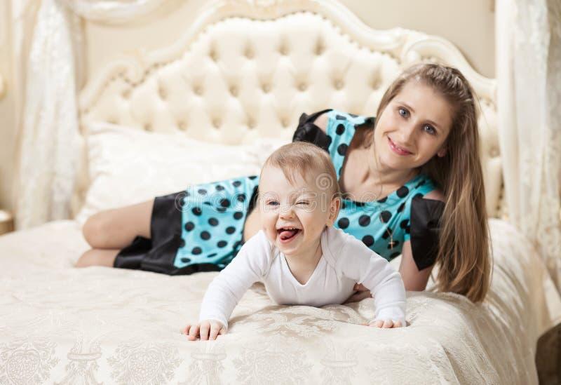Filho caucasiano novo da mãe e do bebê que tem o divertimento na cama foto de stock royalty free