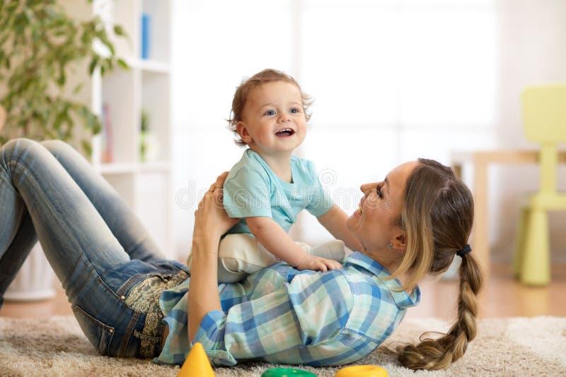 Filho da mãe e do bebê que tem um divertimento no assoalho em casa Mulher e criança que relaxam junto fotografia de stock royalty free
