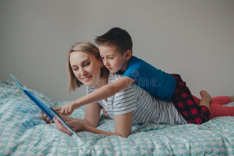 Filho da mãe e do menino em casa que lê o livro imagem de stock royalty free
