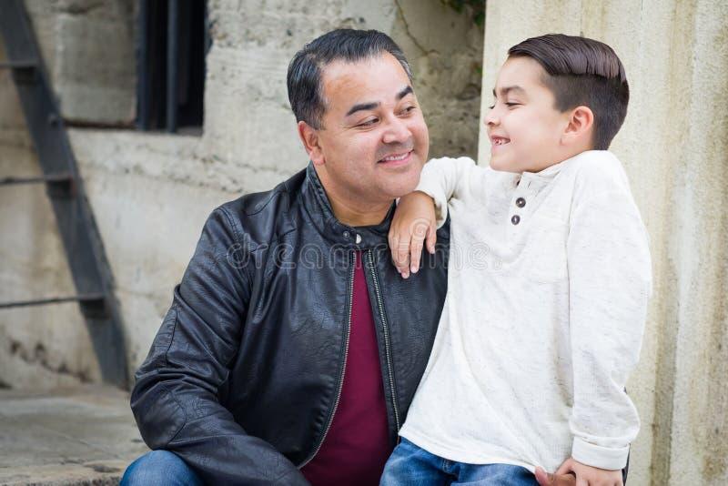 Filho da raça misturada e pai caucasianos latino-americanos Having um Chatp foto de stock