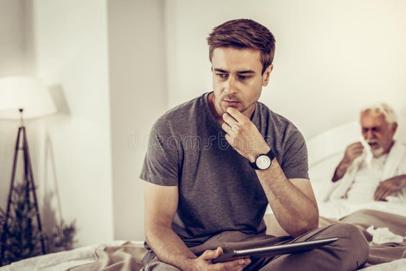 Filho da virada que pensa sobre o diagnóstico de seu paizinho tossindo fotos de stock royalty free