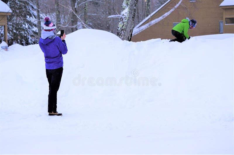 Filho das fotografias da mãe que joga na neve fotografia de stock