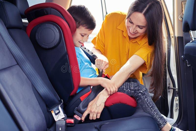 Filho de ajuda da mamã lindo para prender o cinto de segurança imagens de stock royalty free