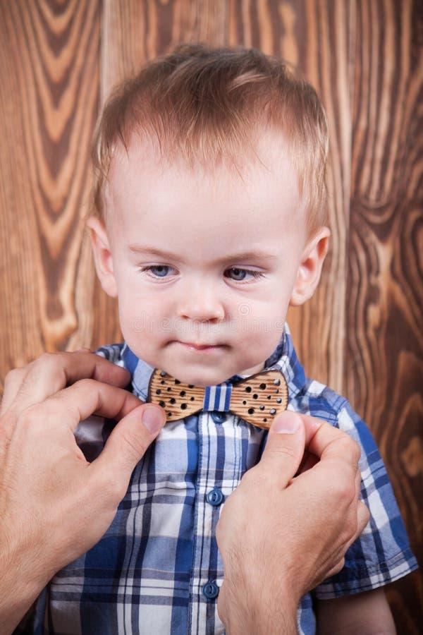 Filho de ajuda do pai para ajustar um laço imagem de stock royalty free
