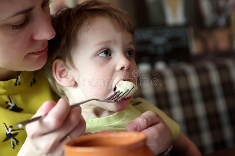 Filho de alimentação da mãe com bolinhas de massa imagem de stock royalty free